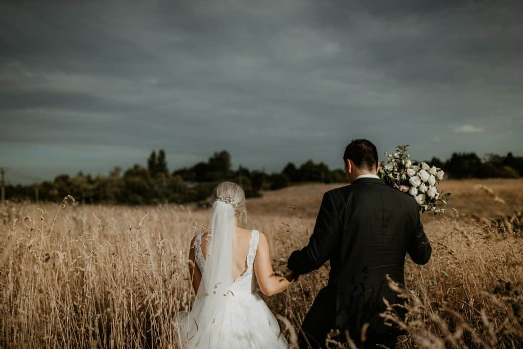 bride and groom walking in field of long grass